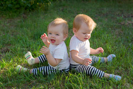 Twin girls are sitting on the green grass with their backs to each other.