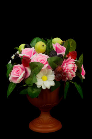 Exclusive handmade soap in the form roses peonies daisies berries and fruits in a vase on a black background.