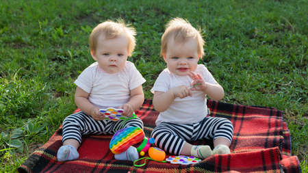Twin girls play with bright toys on a blanket in a city park.