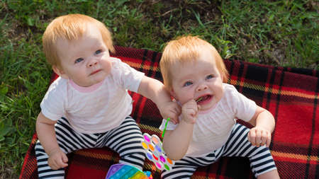 Two twins a blanket with bright toys look up. 版權商用圖片