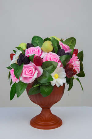 A vase with handmade soap in the shape of flowers raspberries blackberries and pears on a white background.