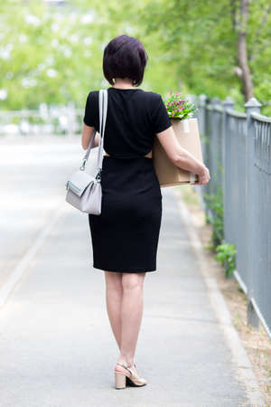 A fired brunette in a black dress with a box of personal belongings. 版權商用圖片