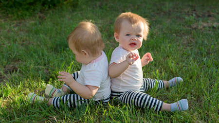 Twin girls are sitting on green grass with their backs to each other.