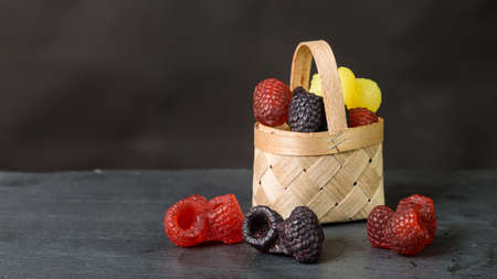 Handmade soap basket in the form of blackberries and raspberries on a black backgroun. Copy space