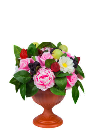 A vase with handmade soap in the shape of flowers raspberries blackberries and pears on a white background. Isolated