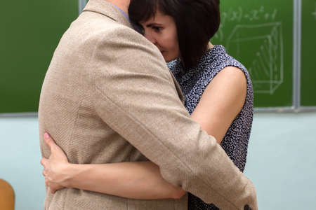 A man and a woman embrace in a school classroom at the blackboard.