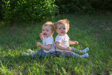 Portrait of twin sisters sitting on the grass with their backs pressed against each other.