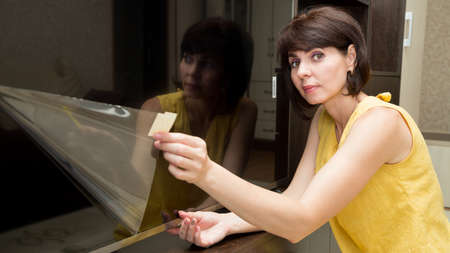 A brunette in a yellow dress in apartment with a smile takes a film from a new large LCD TV. 版權商用圖片