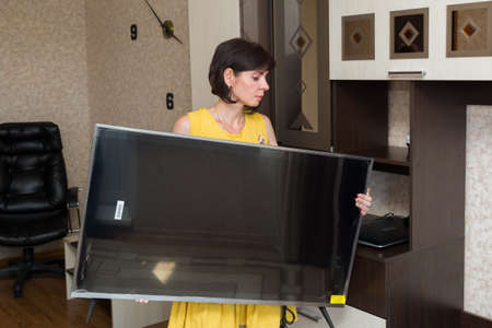 A woman with great difficulty brings a new large LCD TV into the apartment.