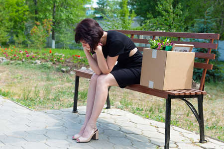A frustrated brunette secretary is sitting on a bench with a box of personal belongings.