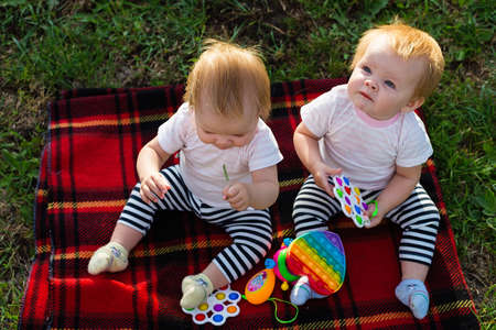 Two twins on a blanket with bright toys look up. 版權商用圖片