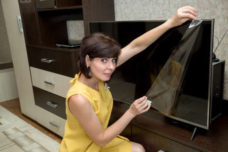 A brunette in a yellow dress in an apartment with a smile takes a film from a new large LCD TV.
