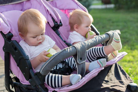 Twin children eat fruit. The concept of proper baby food.