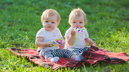 Two twin girls play with colored toys a blanket on a sunny summer day.