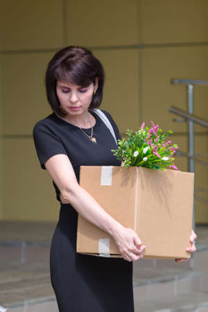 A fired upset brunette lawyer leaves office with a box of personal belongings.