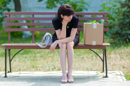 A frustrated brunette secretary is sitting on bench with a box of personal belongings.