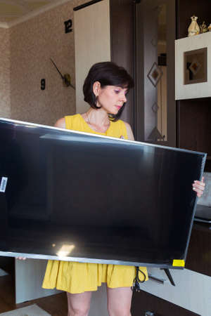 A woman with great difficulty brings new large LCD TV into the apartment.