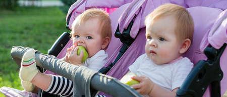 Twin children eat fruit The concept of proper baby food. 版權商用圖片