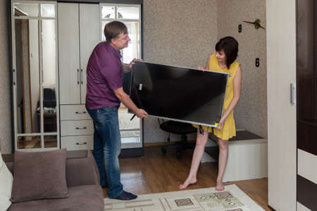 A man and a woman are happy to bring a new large LCD TV into the apartment.