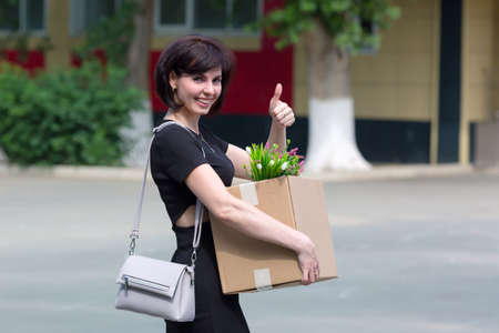 A happy brunette woman with a box of personal belongings shows with a hand gesture that she was hired. 版權商用圖片