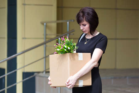 A fired upset brunette lawyer leaves the office with a box of personal belongings.