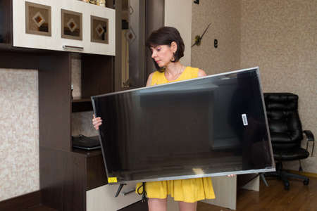 A woman with great difficulty brings a new large LCD TV into apartment.