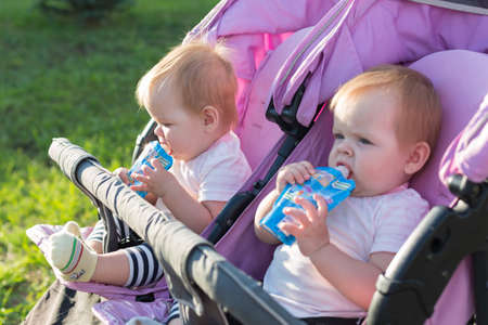 Portrait of hungry twin girls on street with mashed potatoes in their hands.