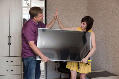 A man a woman are happy to bring a new large LCD TV into the apartment. 版權商用圖片