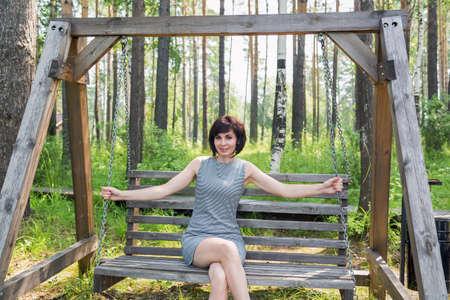 A happy brunette in a striped dress rides on a swing in birch grove.