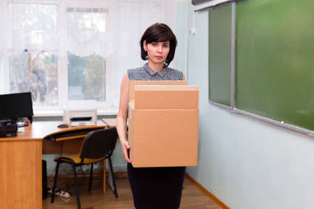 Fired sad teacher leaves the school office with a box of things.