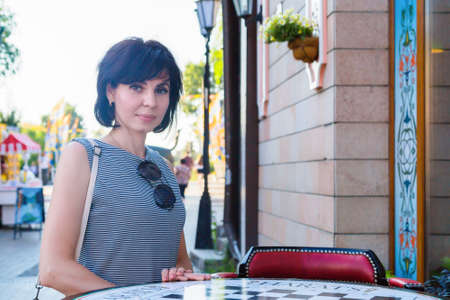 A brunette woman stands near table of a street cafe in a European city on a busy street.