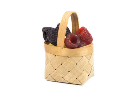 Pieces of handmade soap in the form of raspberries in a wooden basket on a white background. Isolated 版權商用圖片