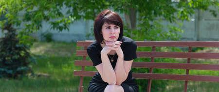 Sad sad adult brunette woman in black dress on a bench.