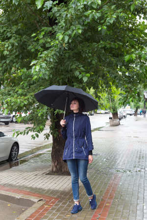 A woman on the street with an umbrella in her hands looks into distance with the hope of seeing a friend. 版權商用圖片