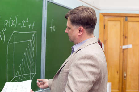 Mathematics teacher writes in chalk on blackboard with his back to the class.