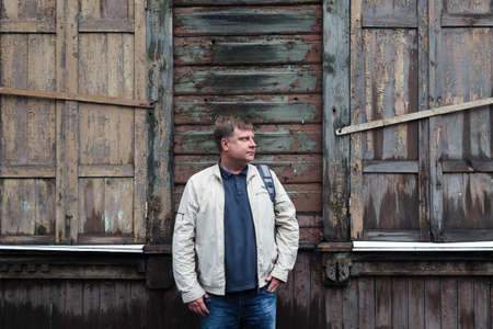 Country man farmer stands near an empty abandoned wooden building.