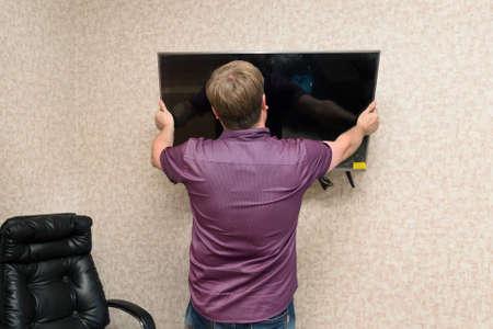 Husband fixing new LCD TV on wall in the room. 版權商用圖片