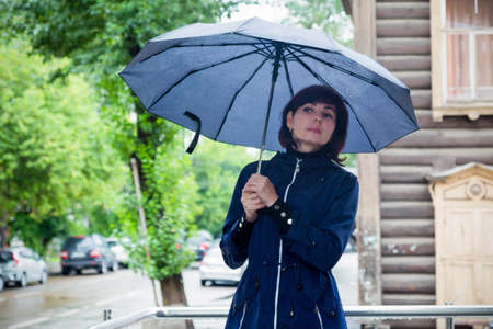 A woman on the street with an umbrella in her hands looks into the distance with the hope of seeing a friend. 版權商用圖片