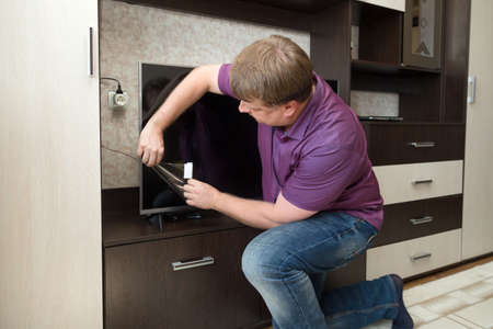 A satisfied blonde man removes a protective film from newly purchased LCD TV.