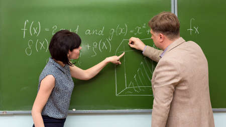 A student at the blackboard at the institute at the department passes an exam in mathematics to the teacher actively explaining her solution to the problem. 版權商用圖片