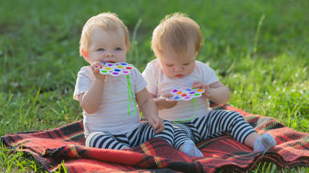 Sisters babies in light clothes sit in park on the grass without parents. 版權商用圖片