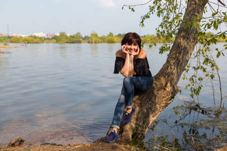 A beautiful female tourist is resting sitting on a tree near the river.