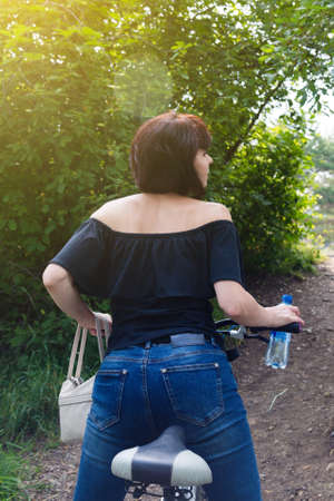 A brunette woman on a bicycle arches her back like a cat beautiful athletic figure. 版權商用圖片