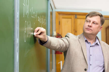 Professor of the Department of Applied Mathematics in the classroom at the blackboard writes formulas for students.