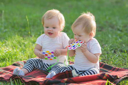 Sisters babies in light clothes sit in the park on grass without parents.