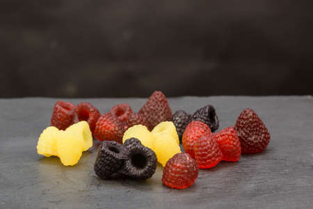 Bright scattered handmade soap in form of raspberries and blackberries, strawberries on a gray background.