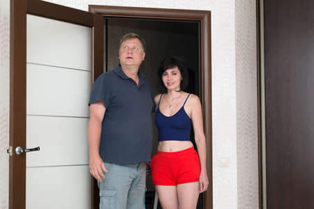 An adult married couple tourists are happy to look at their hotel room.