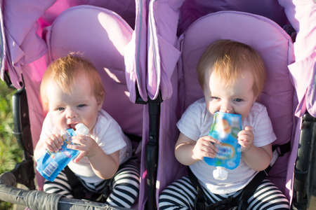 Two hungry children on a sunny summer day with mashed potatoes in their hands in a baby carriage on the street. 版權商用圖片