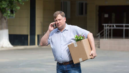 A fired manager with a box of personal belongings on street calls an ad in search of a new job. 版權商用圖片
