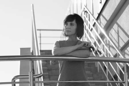 A brunette in a striped dress smiling stands on the stairs leaning her elbows on the railing and holding glasses in her hands. Black and white